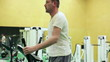 Young man exercising on elliptical cross trainer in gym