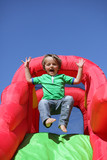 Child on inflatable bouncy castle slide