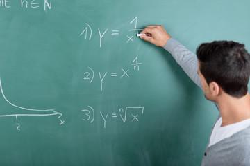lehrer schreibt eine formel an die tafel