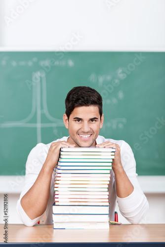 student mit einem stapel bücher