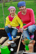 Gardening - mother and daughter  sowing seeds into the soil
