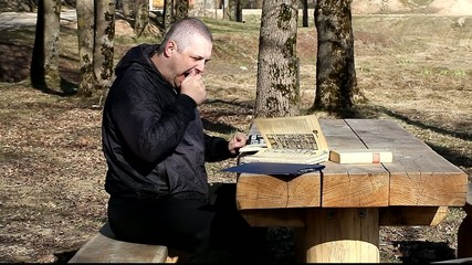 Tired man reading a book outdoors