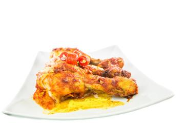 Tandoori chicken in a plate over white background