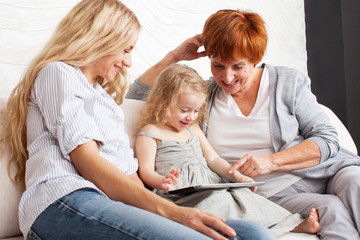 Family wiht tablet computer at sofa