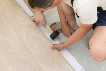 Two workers assembling laminate floor using a hammer