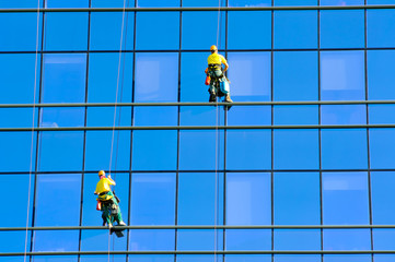 Washers wash the windows of modern skyscraper