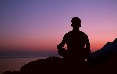 Sitting man silhouette in meditation pose