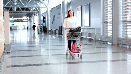 Young Caucasian woman pulling luggage hand-cart in airport