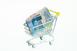 Indonesian Rupiah in shopping cart over white background