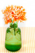 Orange chrysanthemums in a green vase