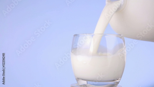 Milk being poured from plastic bottle to glass