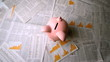 Pink piggy bank falling over sheets of paper