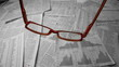 Glasses falling over sheets of paper showing graphs and data