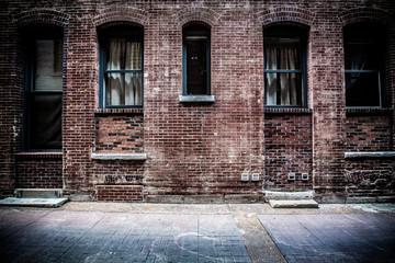 Old brick alleyway with metal doors and windows
