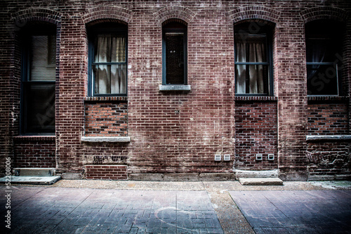 Old brick alleyway with metal doors and windows