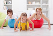 Healthy family exercising with push up on large balls