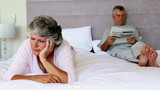 Woman worried about something while her husband is reading newspapers