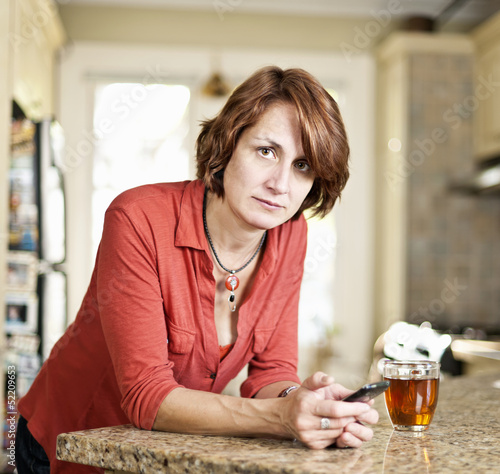 Concerned mature woman in kitchen