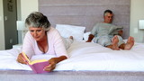 Mature couple reading in the bedroom