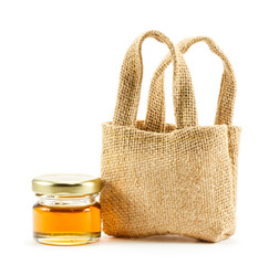 Sackcloth bag and honey on white background