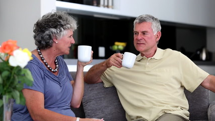 Mature couple chatting  together with a cup of coffee