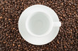 Ceramic cup and plate over coffee beans