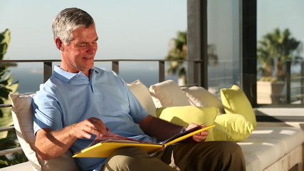 Mature man looking at picture album on the balcony