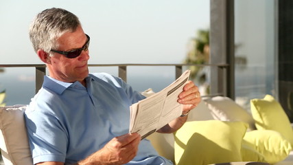 Mature man taking off his sunglasses while reading newspaper