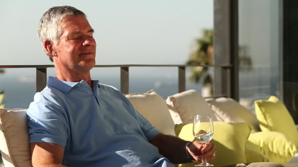 Man drinking a glass of wine while sunbathing