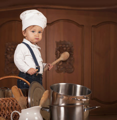 boy in a cook cap among pans and vegetables in kitchen