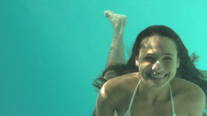 Smiling woman swimming underwater