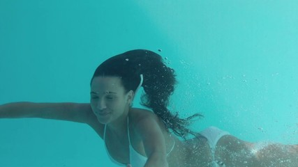 Smiling brunette swimming underwater and looking at camera