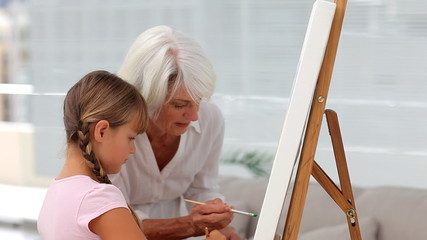 Granny and granddaughter painting together