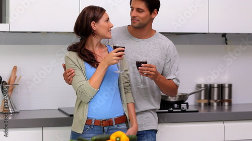 Couple chatting and toasting in the kitchen