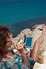 Donna al mare con un tablet