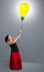 Pretty lady holding a light bulb balloon