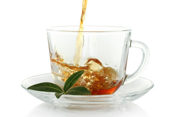 Tea pouring into cup with green leaves on a white background .