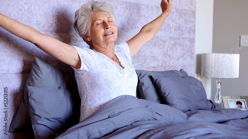 Old woman waking up and stretching