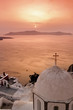 Santorini with Fira Church against sunset over sea.