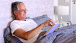 Elderly man reading book in bed