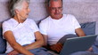Elderly couple doing something on the laptop