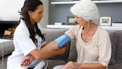 Home nurse checking her elderly patients blood pressure