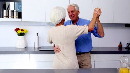 Couple waltzing together in kitchen