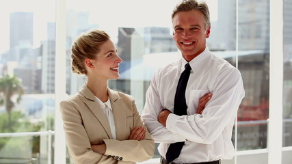 Standing business people with arms folded