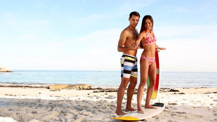 Man teaching to an attractive woman how to surf