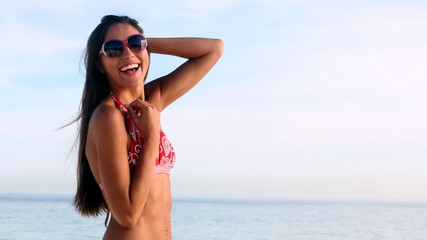 Smiling woman posing on the beach with sunglasses