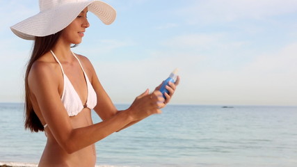 Woman with hat applying sunscreen protection