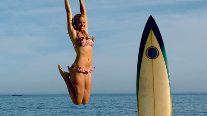 Blonde woman jumping beside her surfboard