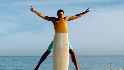 Attractive man hiding behind his surfboard