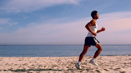 Attractive man running on the beach
